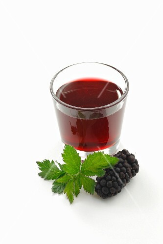 A glass of blackberry syrup, blackberries and blackberry leaves
