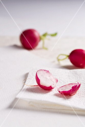 Radishes, whole and sliced in two, on kitchen paper