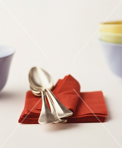 Soup spoons on a stack of red paper napkins