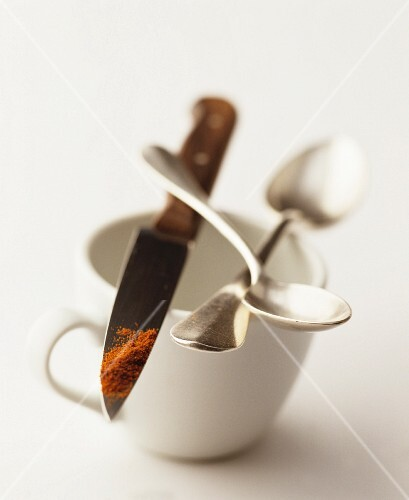 A still life featuring a cup, coffee spoons and ground spice on the end of a knife