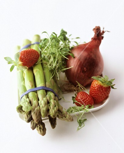 A still life featuring green asparagus, strawberries, an onion and cress