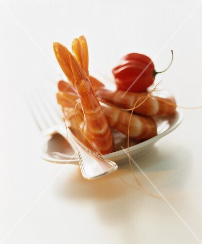 A still life featuring prawns and habanero chillies on a plate
