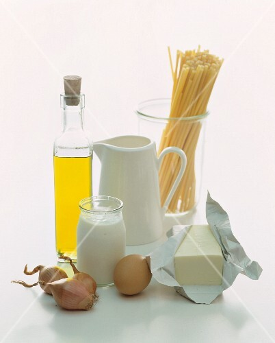 A still life of foodstuffs featuring milk, yoghurt, oil, pasta, an egg and butter