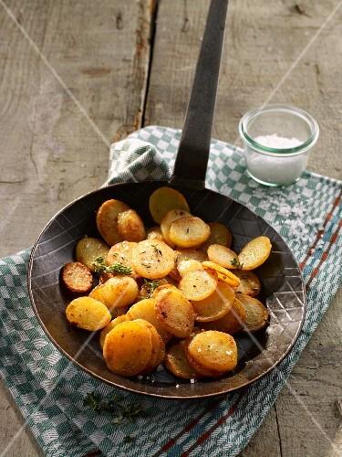 Fried potatoes in a pan on a tea towel