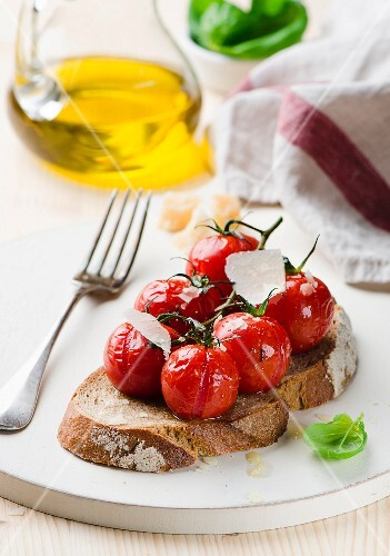 A slice of bread topped with with grilled tomatoes and parmesan