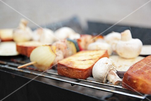 Tofu slices and vegetable skewers with courgette, onions, mushrooms and aubergines on the barbecue