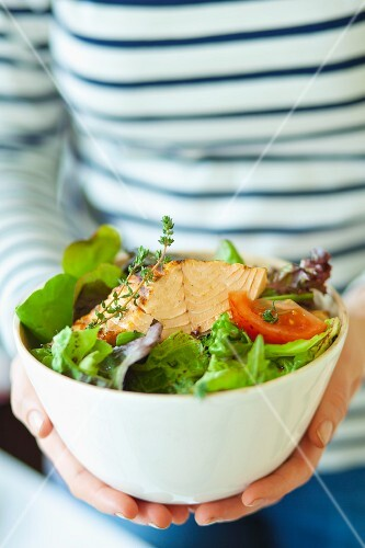 A woman holding a bowl of salad leaves with fried tuna, tomatoes and thyme