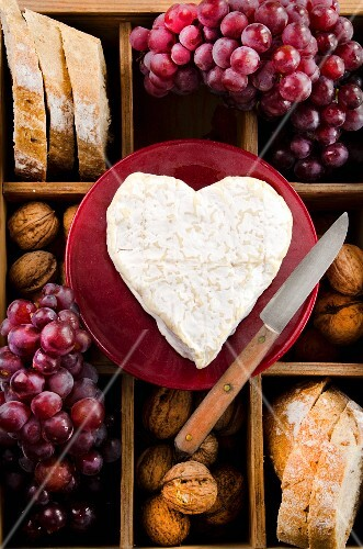 A heart-shaped Neufchatel cheese on a wooden crate with bread, nuts and red grapes