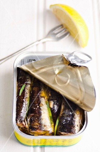 An open tin of sardines with a wedge of lemon