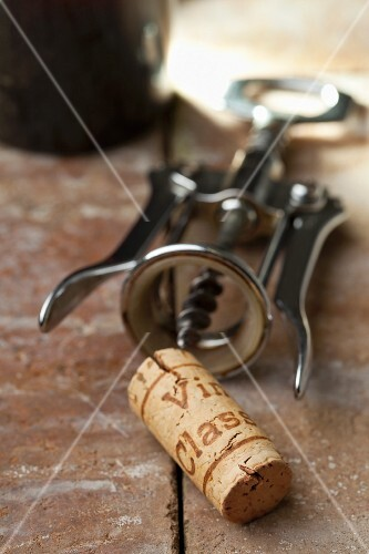 A wine cork with a corkscrew and a bottle of wine