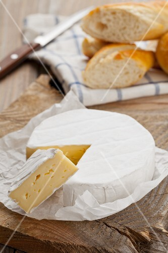 Camembert, one slice cut, on a wooden platter with chunks of baguette