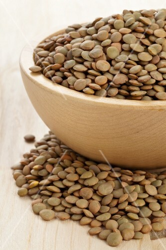 Dried green lentils in a wooden bowl
