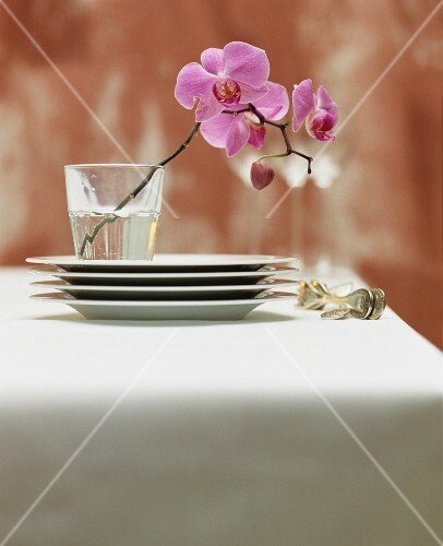 A stack of plates and silver cutlery next to a glass holding purple orchid flowers