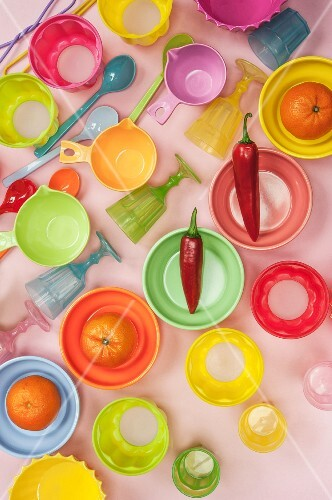 Colourful rows of plastic bowls, spoons and glasses with tangerines and red chillies