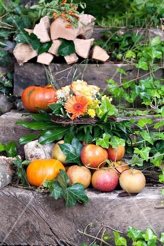 Apples, pumpkins and firewood on garden steps