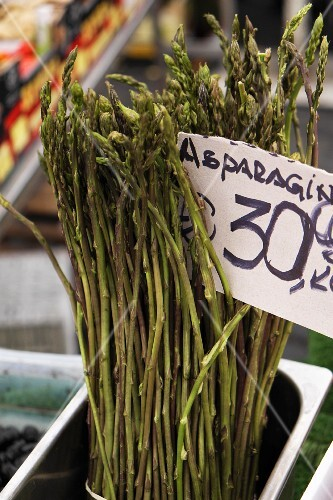Wild asparagus at the market with a price sign