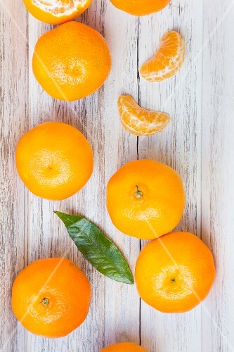 Sections of and whole clementine oranges and a leaf