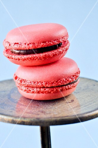 Two raspberry macarons with chocolate filling