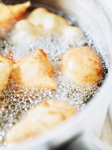 Mutzen (German Karneval pastries) being fried in hot oil