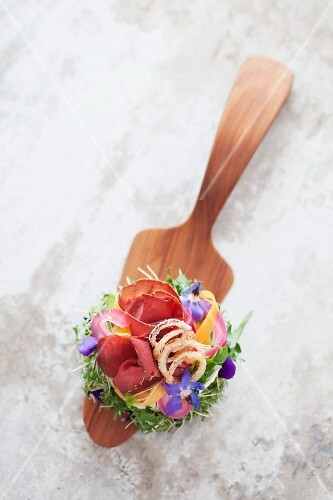 A canapé of bread topped with cream cheese, smoked elk, onions and borage flowers, on a cake slice