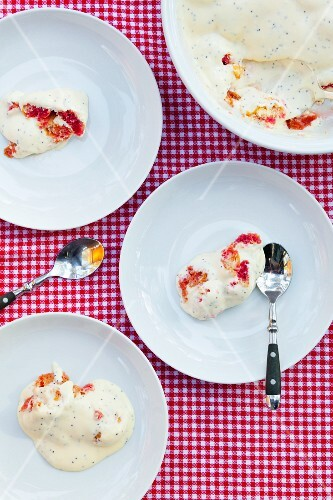 Several dessert dishes filled with raspberry cake topped with vanilla-poppy sauce