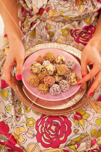 A woman holding a plate of chocolates coated with almonds, coconut and chocolate flakes