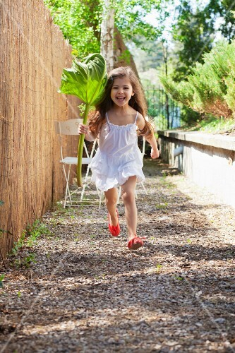 Little girl running along next to garden fence holding rhubarb leaf