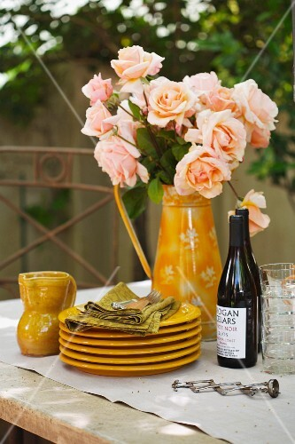 Stacked plates, salmon pink roses and bottles of wine on table in garden