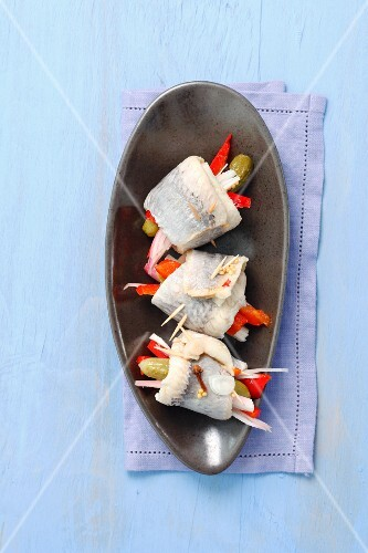 Rollmops with strips of pepper and pickled gherkins (view from above)