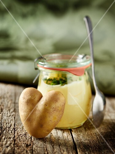 A heart-shaped potato by a jar of mashed potato