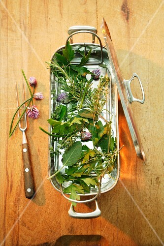 Fresh herbs in a fish cooking dish with insert