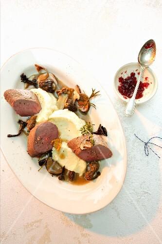 Saddle of venison on mashed potato with mushrooms and cranberry jam