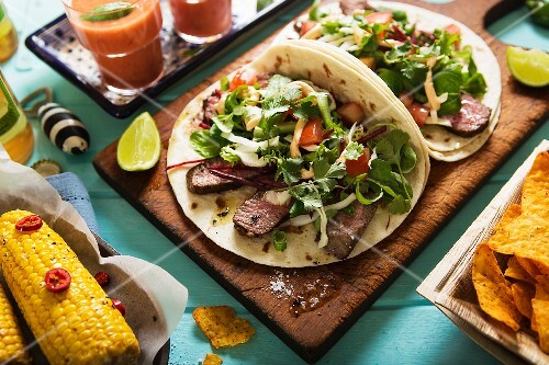 Mexican dishes: tortillas with beef and salad, corn cobs with chilli