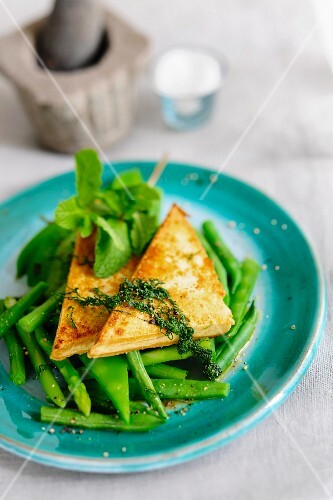 Lemon tofu on a bed of asparagus and beans