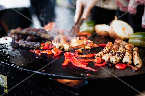 Spare ribs, sausages and vegetables on the barbeque