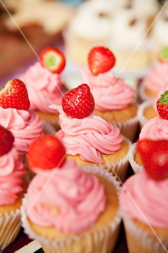 Several cupcakes with strawberry frosting