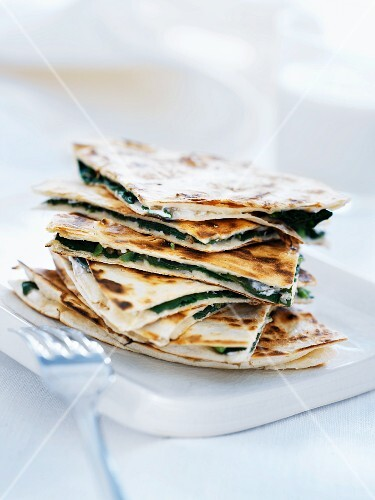 Several slices of spinach pizza, stacked