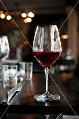 A glass of red wine on a table in a restaurant