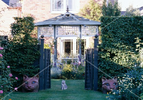 A cat and cat figures by the garden gate of an English country house with a summer house