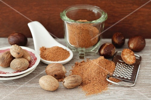 A still life featuring whole, ground and grated nutmeg
