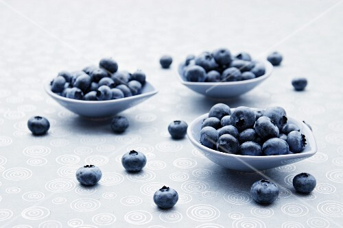 Fresh blueberries in bowls and alongside