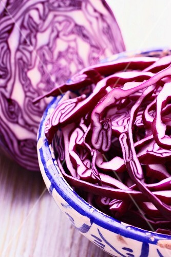 Sliced red cabbage in a bowl in front of half a red cabbage