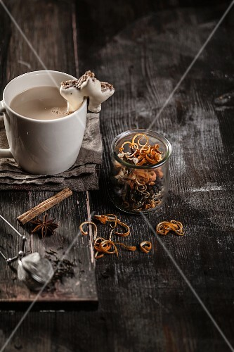 Masala chai in a cup with biscuits and chai spices in a glass
