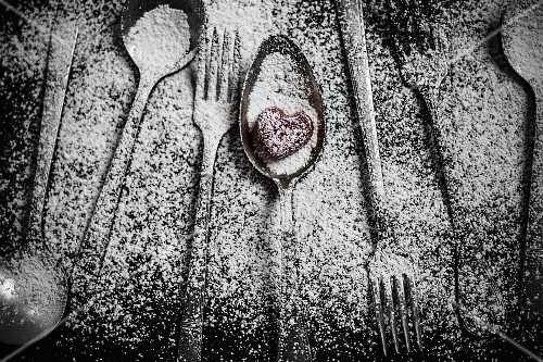 Cutlery dusted with icing sugar, a heart-shaped sweet on a spoon