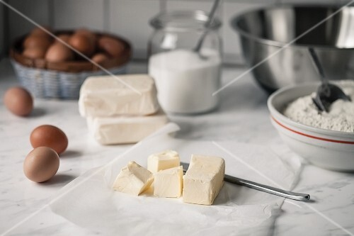 Chunks of butter, flour, sugar and eggs for baking biscuits