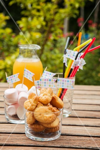 Baked treats, marshmallows and drinking straws decorated with flags for a child's birthday