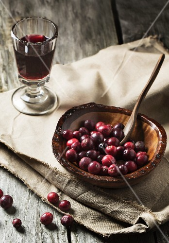 Wooden bowl of cranberries with glass of berry wine