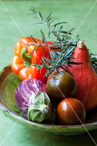 Assorted types of vegetables and fresh rosemary in a clay bowl