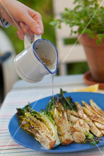 Grilled vegetables being marinated in a herb dressing