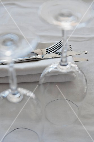 Cutlery on top of a napkin and upturned wine glasses on a table in a restaurant